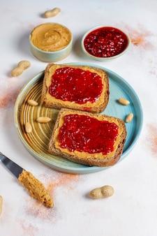 라즈베리 잼을 곁들인 땅콩 버터 샌드위치 또는 토스트.