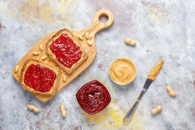 Panini al burro di arachidi o toast con marmellata di lamponi.