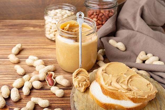 Peanut butter in spoon near creamy peanut paste in open glass jar and slice of peanut butter bread toast.