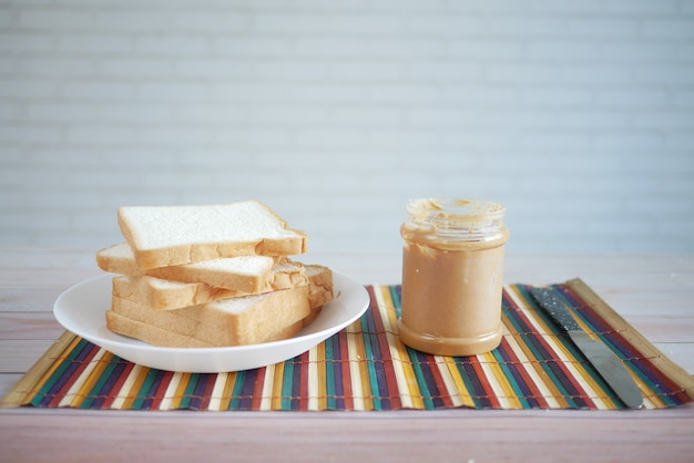 Peanut butter and stack of bread on table with copy space