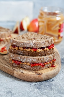 Peanut butter and strawberry jelly sandwich with apple