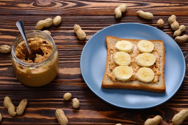 나무 배경에 바나나 조각을 넣은 땅콩 버터 토스트