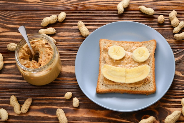 Peanut butter toast with banana slices  on wooden background