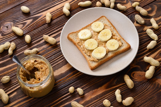 Peanut butter toast with banana slices  on wooden table