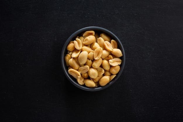 어두운 배경에 그릇에 땅콩 덩어리입니다. 목업