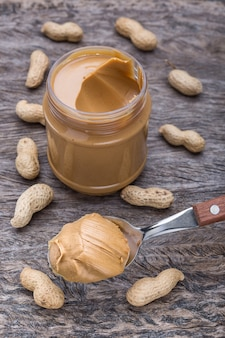 Peanut cream in spoon. on a background of nuts and container, vertical.