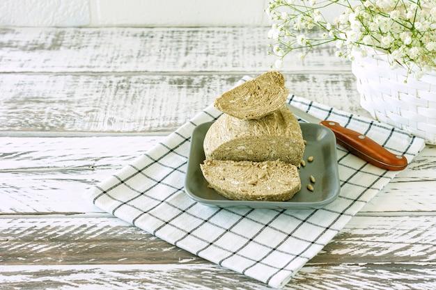 Халва арахисовая на тарелке на белом деревянном столе. восточный десерт из орехов и семян с сахарным сиропом.