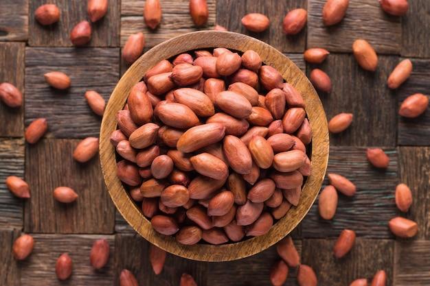木製のテーブルの背景にボウルで皮をむいたピーナッツ インド。
