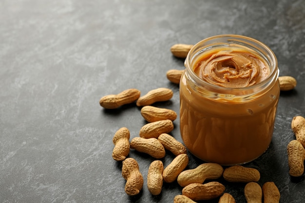 Peanut and jar with peanut butter on black smoky background Premium Photo