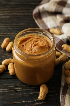 Peanut, napkin and jar with peanut butter on wooden background