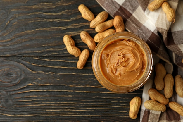 Peanut napkin and jar with peanut butter on wooden background