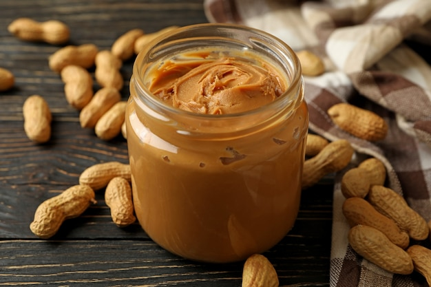 Peanut napkin and jar with peanut butter on wooden background Premium Photo