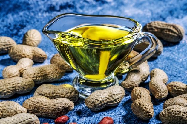 青いテーブルの背景にあるピッチャーのピーナッツオイルは、健康的で食事の栄養に最適です