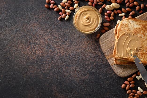 Арахисовая паста и хрустящие тосты на коричневом фоне для здорового завтрака. концепция здорового веганского питания.