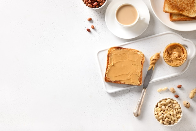 Peanut paste and crispy toasts on white background for healthy breakfast.