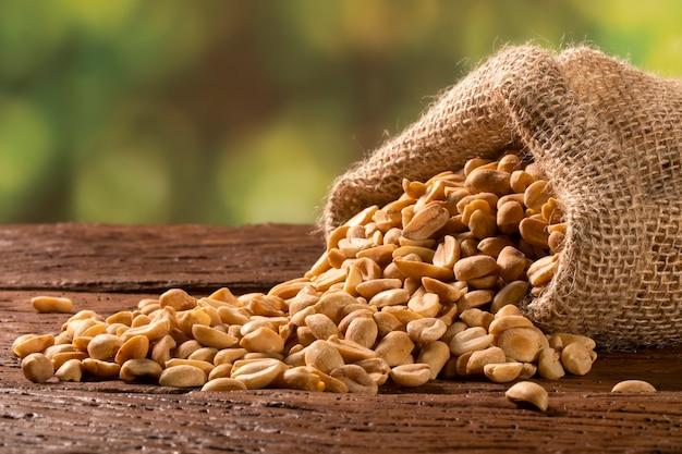 Peanut in sack bag on wooden background.