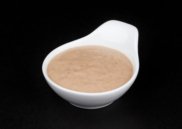 Peanut sauce. tahini in white bowl isolated on black background