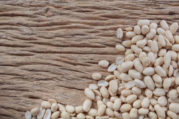 Семена арахиса на деревянном фоне на кухне