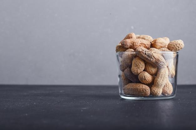 灰色の背景にガラスのカップのピーナッツの殻。