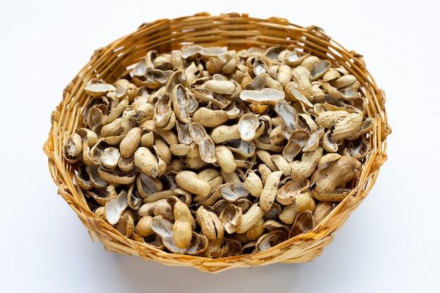 Скорлупа арахиса в бамбуковой корзине на белом