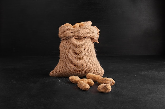 Peanut shells out of a rustic parcel on black background.