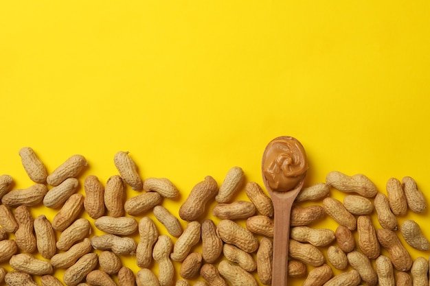 Peanut and spoon with peanut butter on yellow background