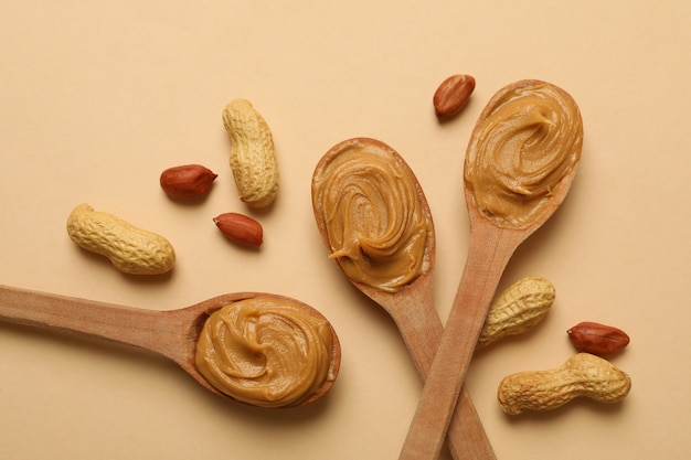Peanut and spoons with peanut butter on beige background