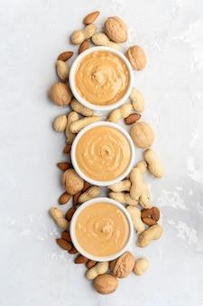 Арахис, миндаль и ореховое масло на бетонном фоне