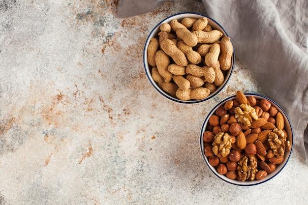 Арахис, миндаль, грецкие орехи. концепция здорового питания, диеты. ассорти из орехов в миске. орехи. Premium Фотографии