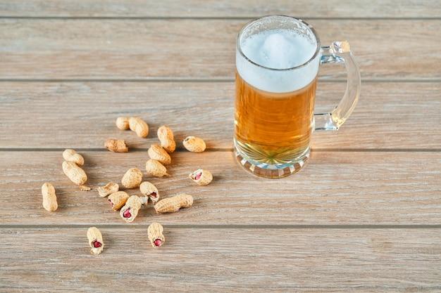 木製のテーブルにピーナッツとビールのグラス。