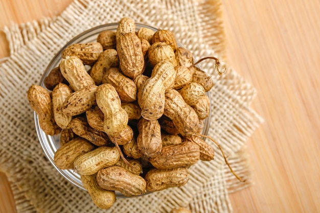 Peanuts in bowl on the wooden background.