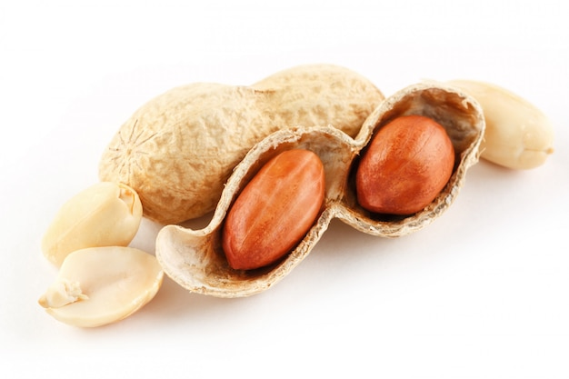 Peanuts closeup in shell and peeled on white