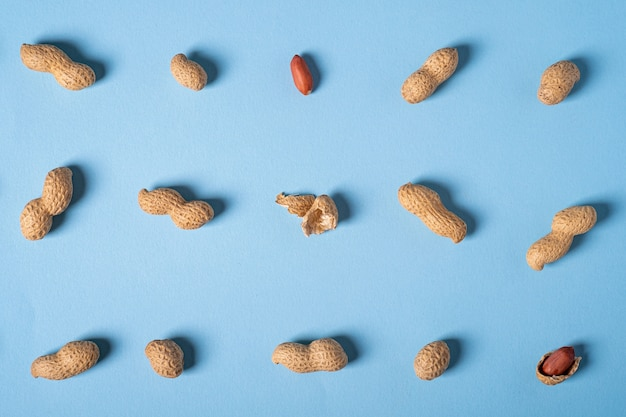Peanuts flat lay minimal on blue background backdrop food nut texture top view