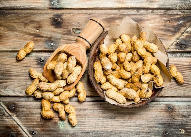 ボウルにピーナッツと木製のテーブルに木製のスクープ。