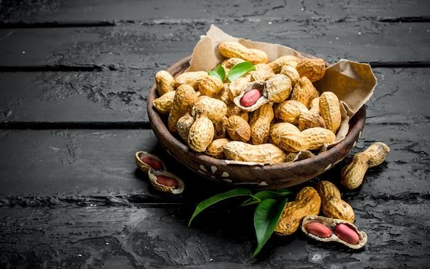 黒い木製のテーブルの上に葉が付いているボウルのピーナッツ。