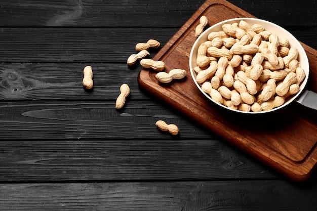 黒い木製の背景の鍋にピーナッツ