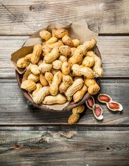 ボウルの中のピーナッツ。木製の背景に。