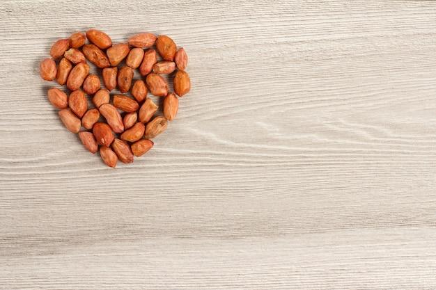 灰色の木の板にハートの形をしたピーナッツ。コピースペースのある上面図