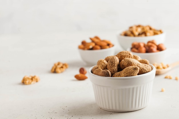 Арахис в скорлупе. ассорти из орехов миндаль, фундук, грецкие орехи. здоровые закуски. скопируйте пространство.
