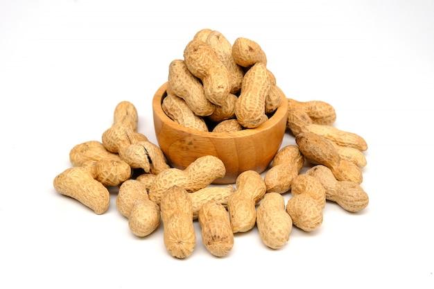 白で隔離される木製のボウルにピーナッツ