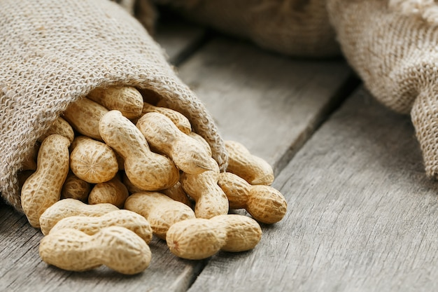 Peanuts in a miniature burlap bag on old, gray wooden surface
