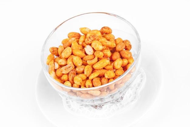Арахис жареный соленый на белом фоне в прозрачной тарелке