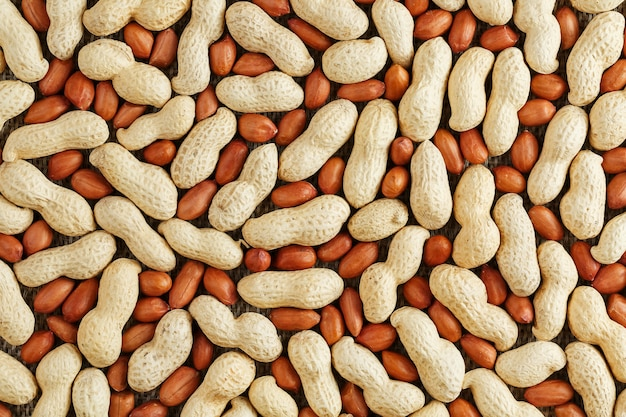 Peanuts in a shell mixed with peeled, the texture of the food background of beans