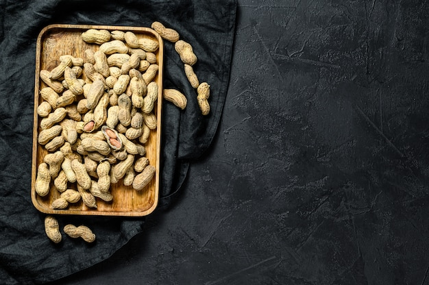 Peanuts in a shell. organic raw groundnut. black background. top view. space for text