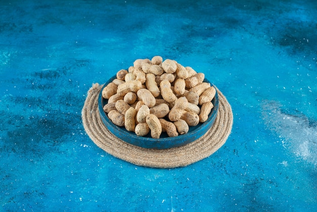 Arachidi in guscio in un piatto di legno sul sottopentola, sul tavolo blu.