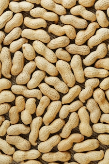 Peanuts in their shell textured food background.