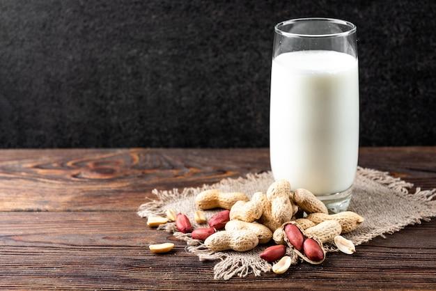 Арахис со стаканом молока на столе