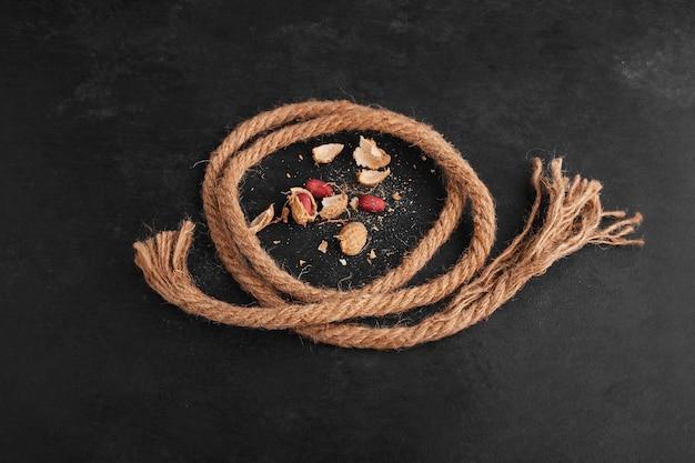 黒い表面に素朴な糸が脇にあるピーナッツ。