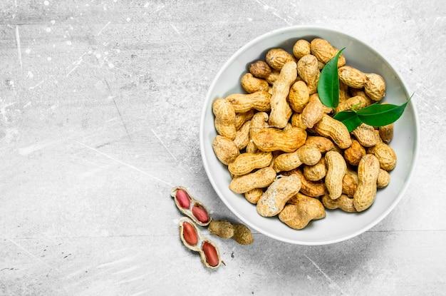 ボウルに緑の葉が入ったピーナッツ。素朴な背景に。