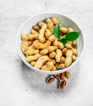 ボウルに緑の葉が入ったピーナッツ。素朴な表面に。